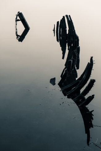 Ribs of a rotting ship in the calm waters of the harbour at Bowling, Scotland